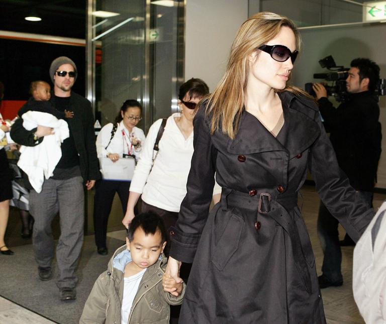 NARITA, JAPAN: Hollywood stars Angelina Jolie (R) and Brad Pitt (L), accompanied by Jolie's children, arrive at Narita Airport in suburban Tokyo, 27 November 2005. The two stars are now here for the promotion of their movie 'Mr. and Mrs. Smith', which will be screened in Japan from 03 December. AFP PHOTO / Yoshikazu TSUNO (Photo credit should read YOSHIKAZU TSUNO/AFP/Getty Images)