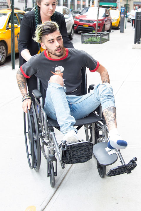 Zayn Malik in a wheelchair after injuring his foot